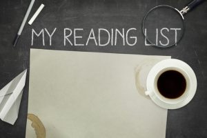 My reading list concept on black blackboard with empty paper sheet and coffee cup